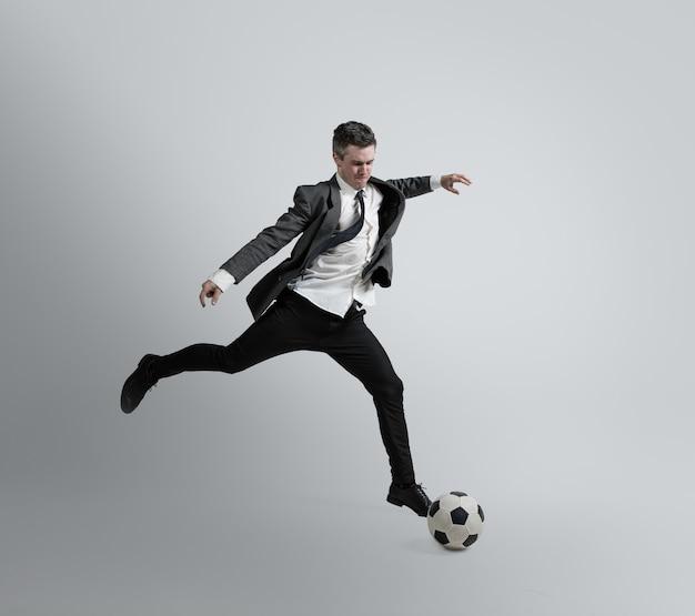 Sueña con la mayor victoria de la vida. hombre en ropa de oficina entrena en fútbol o fútbol con balón en la pared gris. aspecto inusual para hombre de negocios en movimiento, acción. deporte, estilo de vida saludable.