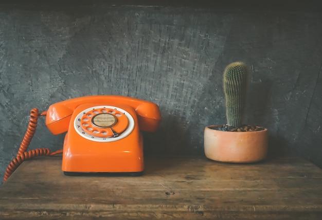 Suena un viejo teléfono naranja con el auricular apagado. teléfono rotatorio retro y cactus en mesa de madera