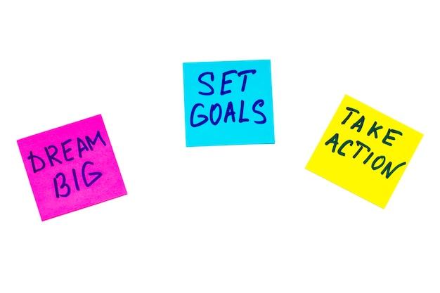 Sueñe en grande, establezca metas, adopte el concepto de acción: consejos motivacionales o recordatorios en coloridas notas adhesivas aisladas en blanco.