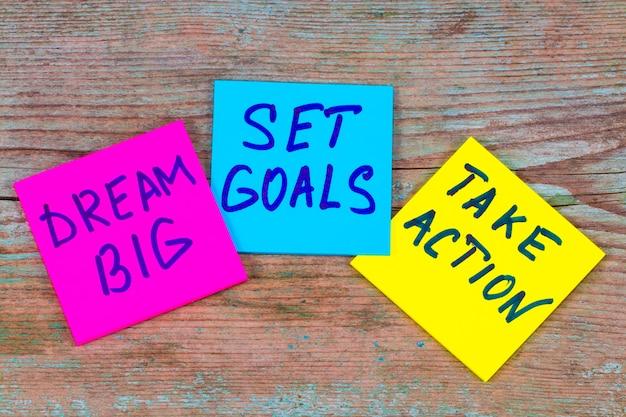 Sueñe en grande, establezca metas, tome el concepto de acción: consejos motivacionales o recordatorios en coloridas notas adhesivas sobre fondo de madera.