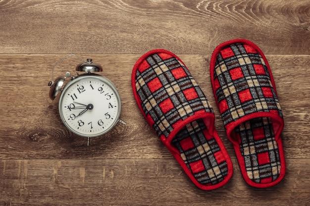 Sueño saludable. zapatillas de interior y reloj despertador en el suelo. vista superior