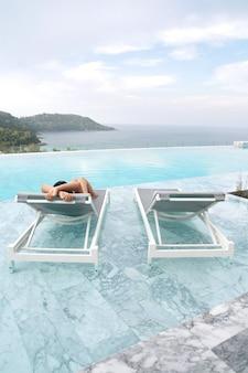 Sueño turístico en tumbona y piscina.