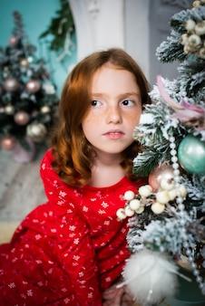 Sueños de niña pelirroja cerca del árbol de navidad.