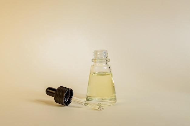 Suero antienvejecimiento en frasco de vidrio con cuentagotas en pared beige. líquido facial esencial con colágeno y péptidos.