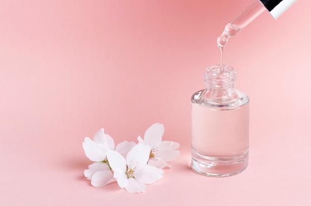 Suero y cuentagotas en un primer plano de fondo rosa, concepto de cosmética natural