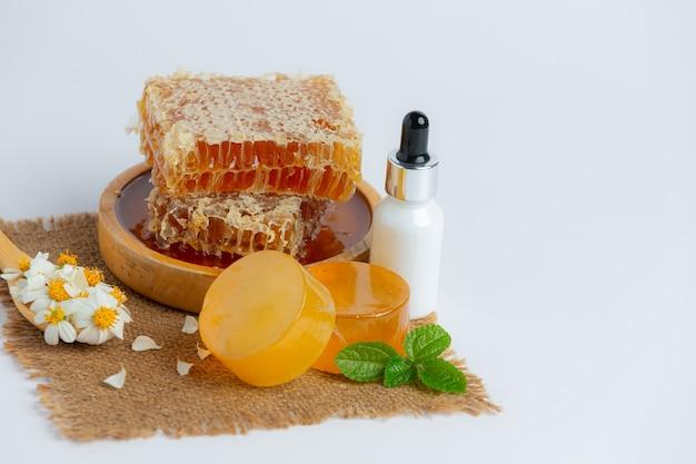 Suero y jabón natural para el cuidado de la piel con miel y panal sobre una superficie blanca.