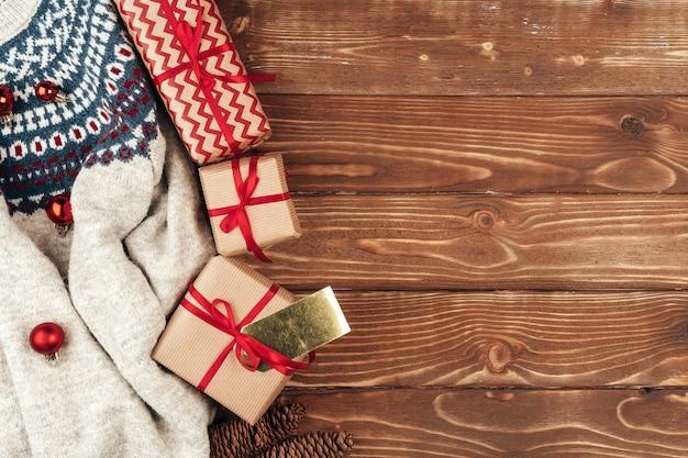 Suéter caliente y regalo de navidad sobre fondo de madera