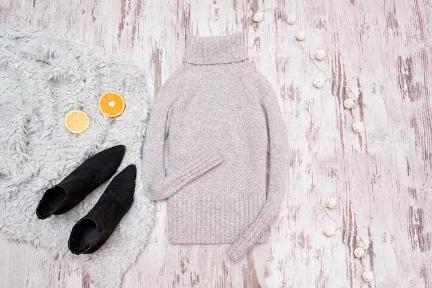 Suéter gris y zapatos negros sobre un fondo de madera