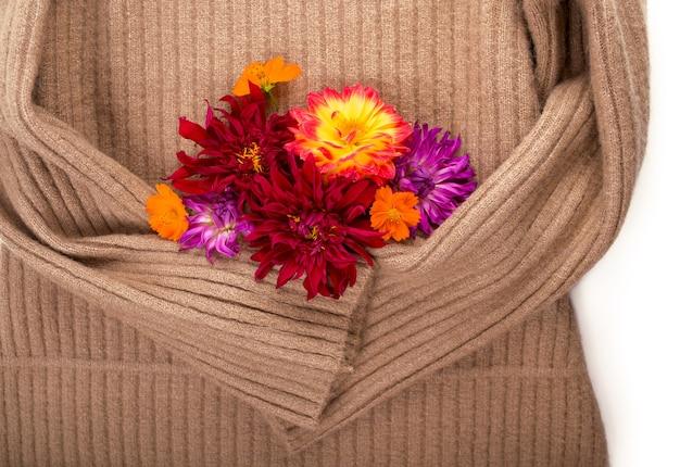 Suéter de lana pelirroja y flores de otoño sobre fondo blanco.