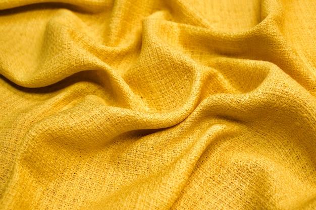Suéter de material de textura de tela cálida amarilla sobre fondo borroso