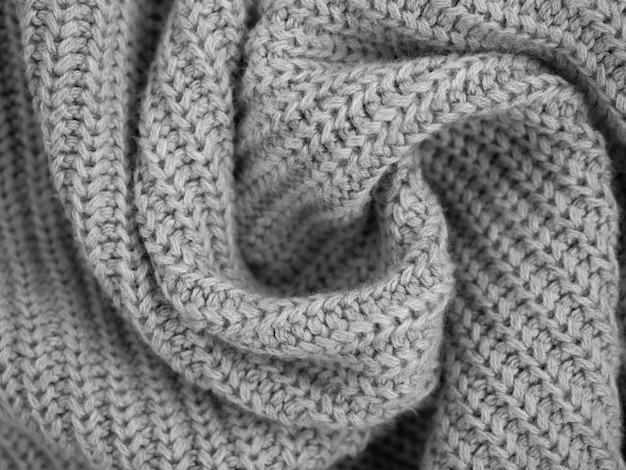 Suéter o bufanda gris cálido de punto. composición acogedora en la atrosfera del hogar. textura de tela de lana gris de moda cerca de fondo. paño de estilo cómodo. material de pliegues ondulados. enfoque suave