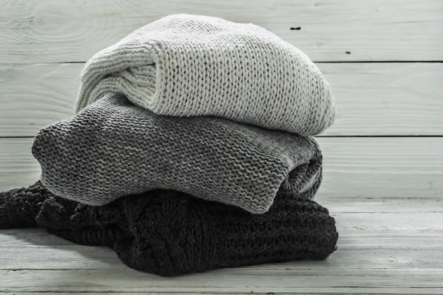 Suéter de punto cálido, tres piezas, negro, gris y blanco en una pared de madera