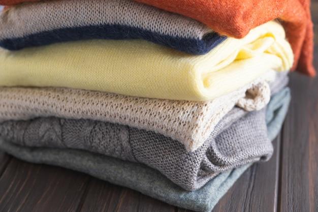 Suéteres acogedores en colores otoñales sobre fondo de madera marrón. diferentes patrones tejidos de cerca.