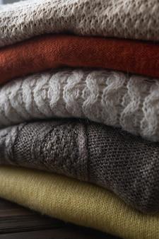 Suéteres acogedores en colores otoñales sobre fondo de madera marrón.