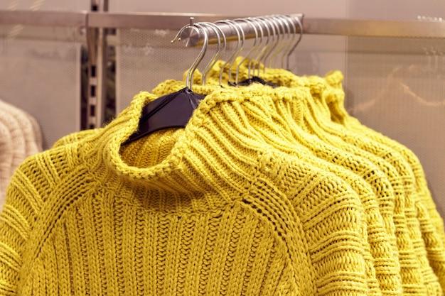 Suéteres amarillos colgados en perchas en la tienda, concepto de compra de ropa