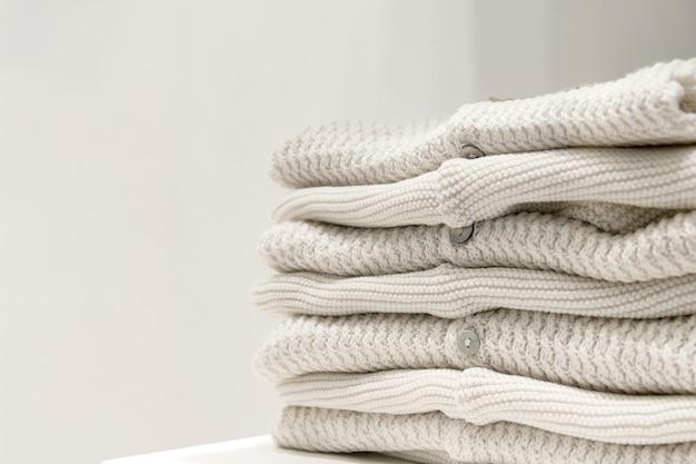 Suéteres beige hechos de telas naturales se doblan sobre la mesa.