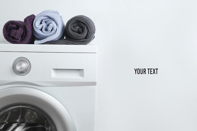 Suéteres enrollados de colores en la lavadora sobre fondo blanco con espacio de copia