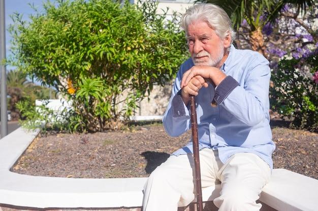 Sufriendo triste hombre mayor sentado al aire libre con un palo para el dolor en las piernas