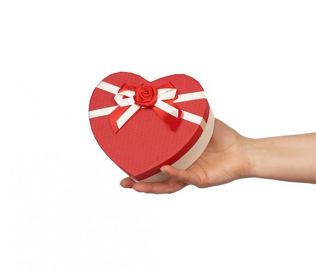 Sujete a mano una caja de regalo roja con lazos de seda atados