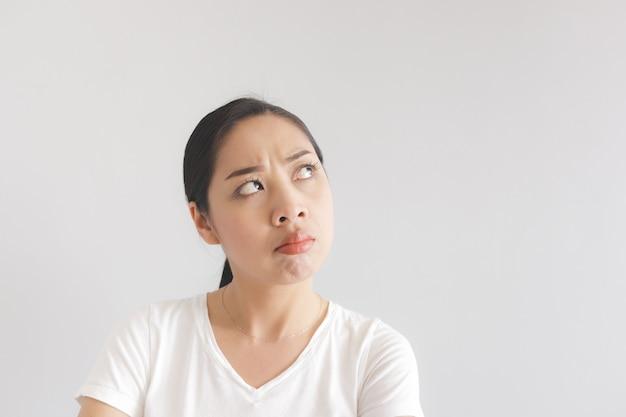 Sulk y gruñón expresión de la mujer de la camiseta blanca. concepto de malhumor ofendido y malhumorado.