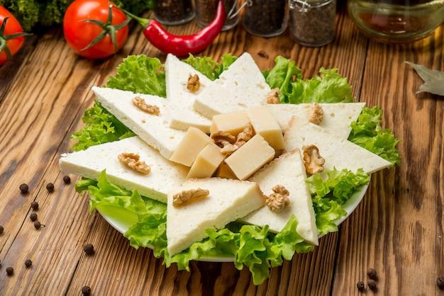Suluguni casero de queso suave con tomate, pimentón, cebolla y albahaca fresca sobre una plancha de madera