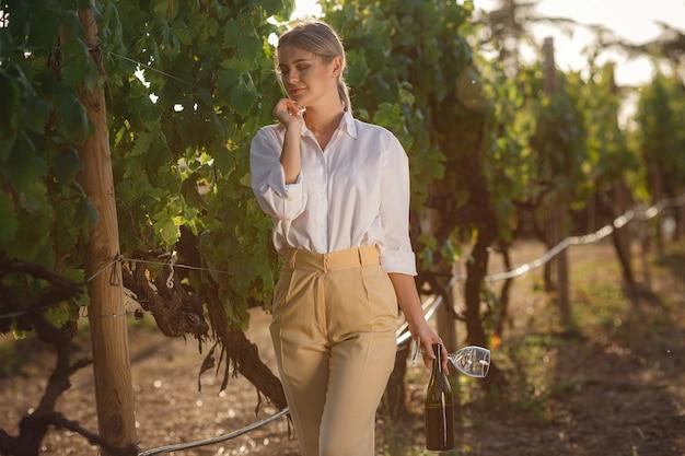 Sumiller de mujer hermosa comprueba las uvas antes de la cosecha