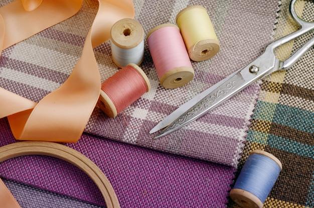 Suministros de costura, agujas, tijeras vintage en el colorido textil de yute