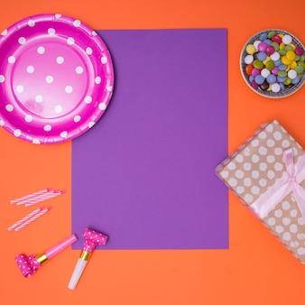 Suministros de cumpleaños femeninos sobre fondo púrpura