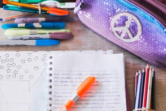 Suministros de escritura y estuche de lápices cerca del cuaderno