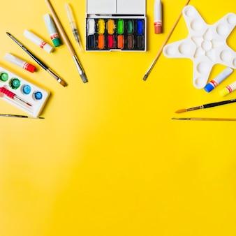 Suministros de pintura sobre fondo amarillo