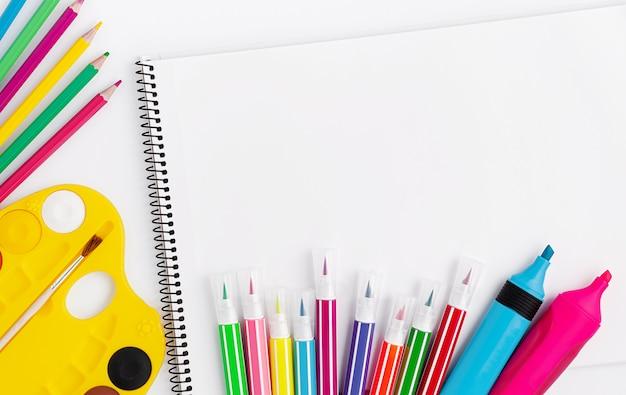 Suministros de dibujo y scetchbook sobre fondo blanco. vista superior, espacio de copia