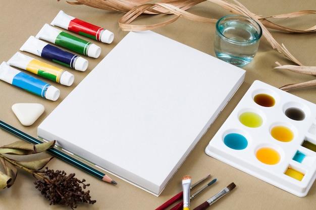 Suministros de dibujo ubicados alrededor de lienzo