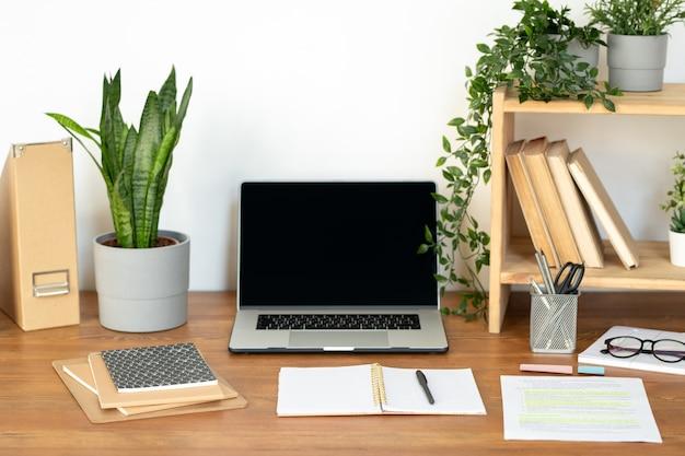 Suministros y equipos para fines comerciales o educativos en un escritorio de madera junto a la pared en la oficina o en el hogar