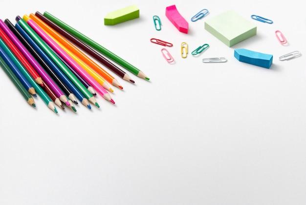 Suministros escolares. lápices de colores, clips de papel de colores en blanco. copie el espacio.