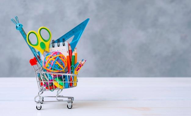 Suministros escolares multicolores en un carrito de compras sobre un fondo gris con espacio de copia de texto. el concepto de regresar a la escuela para el nuevo año escolar, compras.