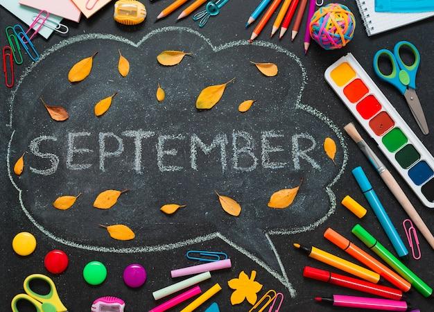 Suministros escolares multicolores, lápices y una nube dibujada con espacio para copiar texto.