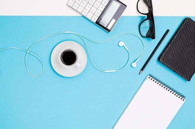 Suministros escolares y de oficina como notas, bolígrafos, lápices, calculadora, pincel, tijeras, café, computadora portátil se encuentran cuidadosamente sobre un fondo blanco y azul