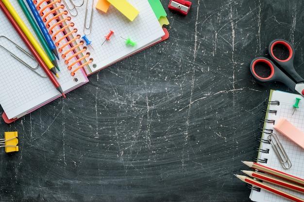 Suministros escolares y de oficina en un fondo de pizarra. espacio libre para texto. vista superior