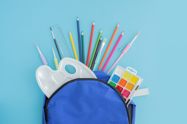Suministros escolares y de oficina sacados de una mochila o mochila azul