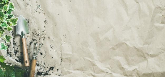 Suministros de jardinería con hiedra en macetas sobre papel artesanal arrugado con espacio de copia, banner largo y ancho