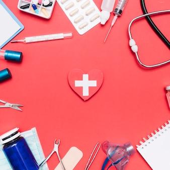 Suministros médicos alrededor del corazón con cruz