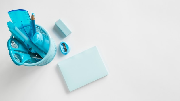 Suministros de oficina azul en taza en mesa