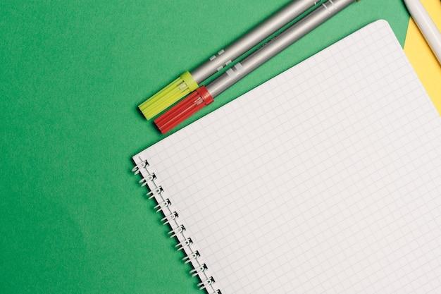Suministros de oficina bolígrafos y blocs de notas sobre fondo verde amarillo