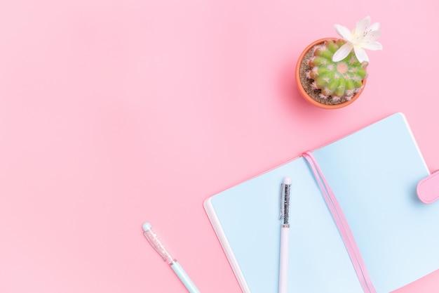 Suministros de oficina de diseño de escritorio de área de trabajo con cactus sobre fondo rosa pastel