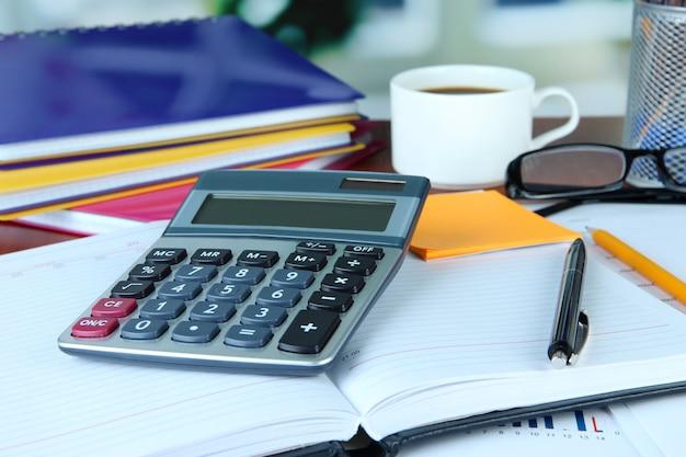 Suministros de oficina con documentos y una taza de café en la mesa de cerca