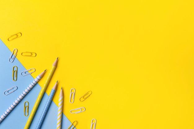 Suministros de oficina escolar en mesa amarilla con espacio de copia.