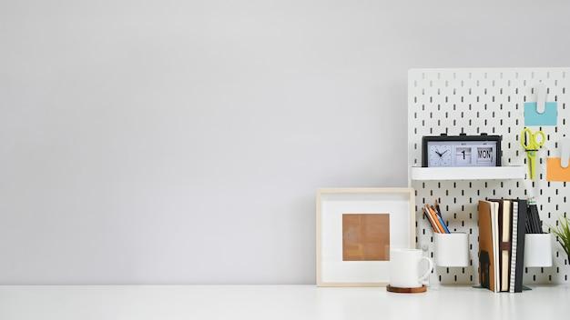 Suministros de oficina de espacio de trabajo, café y marco de fotos en mesa creativa blanca con espacio de copia.