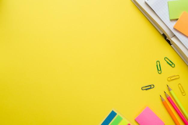 Suministros de oficina en mesa amarilla con espacio de copia.