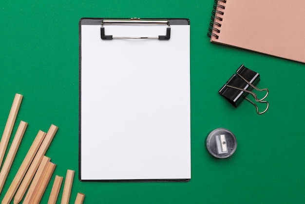 Suministros de oficina y papelería sobre fondo verde