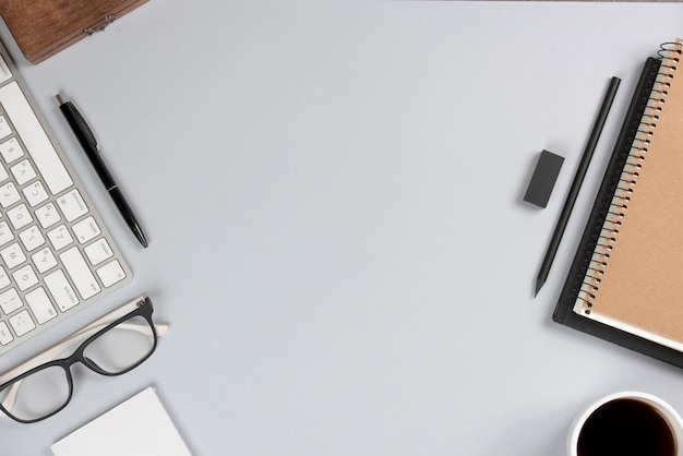 Suministros de oficina con teclado en escritorio gris